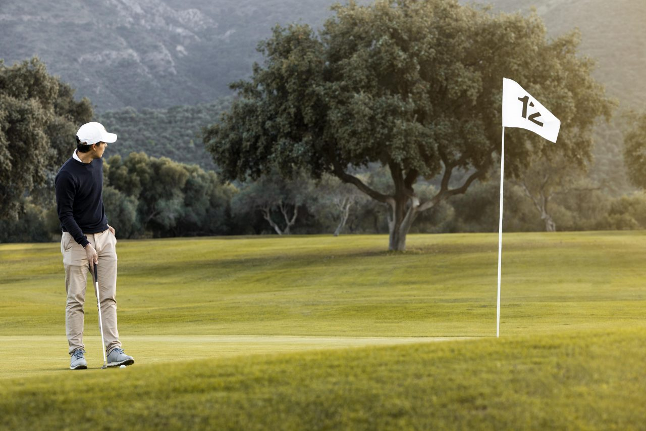 Man On The Golf Field Next To Flag
